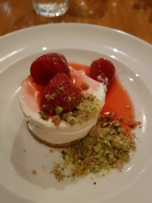 Strawberry cheesecake, summer berry coulis, pistachio dust
